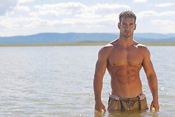sexy man without a shirt standing in a lake