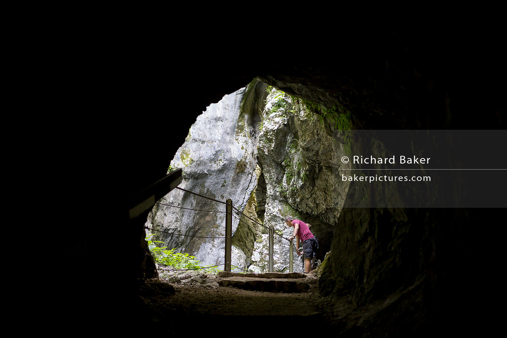 Seen through one of the tunnels, a visitor peers down into Tolmin Gorge (Tolminska Korita), on 20th June 2018, in Tolmin Gorge , Slovenia.