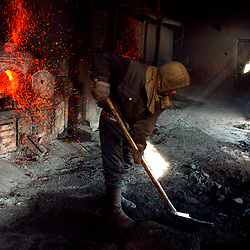 Still in the process of modernizing their infrastructure, the cities still rely on coal fed furnaces to create the steam that heats Mongolian apartments.  A few miles outside the capital, a boy feeds coal into the furnace that supplies his towns heating system.