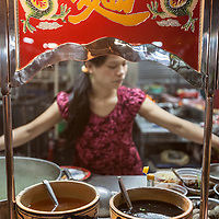 """A cart selling advertising """"麵"""" the traditional Chinese character for  noodles at a night market in Saigon, Vietnam."""