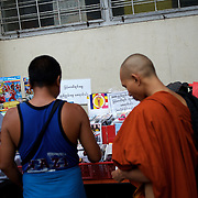 May 19, 2013 - Yangon, Myanmar: A buddhist monk buys goods at a CD stand marked with a sticker emblazoned with 969, the logo that has come to represent Myanmar's anti-Muslim movement. Taxis, buses, shop fronts and street stalls across the country display what some consider a symbol of Buddhist<br />