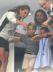 The Duchess of Cambridge with Prince George and Princess Charlotte look through a window at the prize giving after the King's Cup regatta at Cowes on the Isle of Wight.