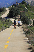 Two people on mountain path walk Coll de Rates, Tàrbena, Marina Alta, Alicante province, Spain