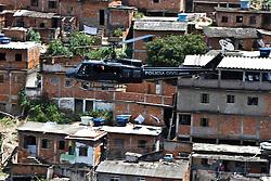 Um helicóptero da polícia civil sobrevoa favela Morro do Alemão em 29 novembro de 2010 no Rio de Janeiro, Brasil. A polícia vasculhou os esgotos em favelas do Rio de Janeiro segunda-feira por centenas de traficantes de drogas que fugiram de um ataque militar sem precedentes sobre as favelas cariocas que rendeu 40 toneladas de entorpecentes, mas poucas prisões. FOTO: Jefferson Bernardes/Preview.com