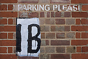A No Parking stencil sign on a brick wall in London.