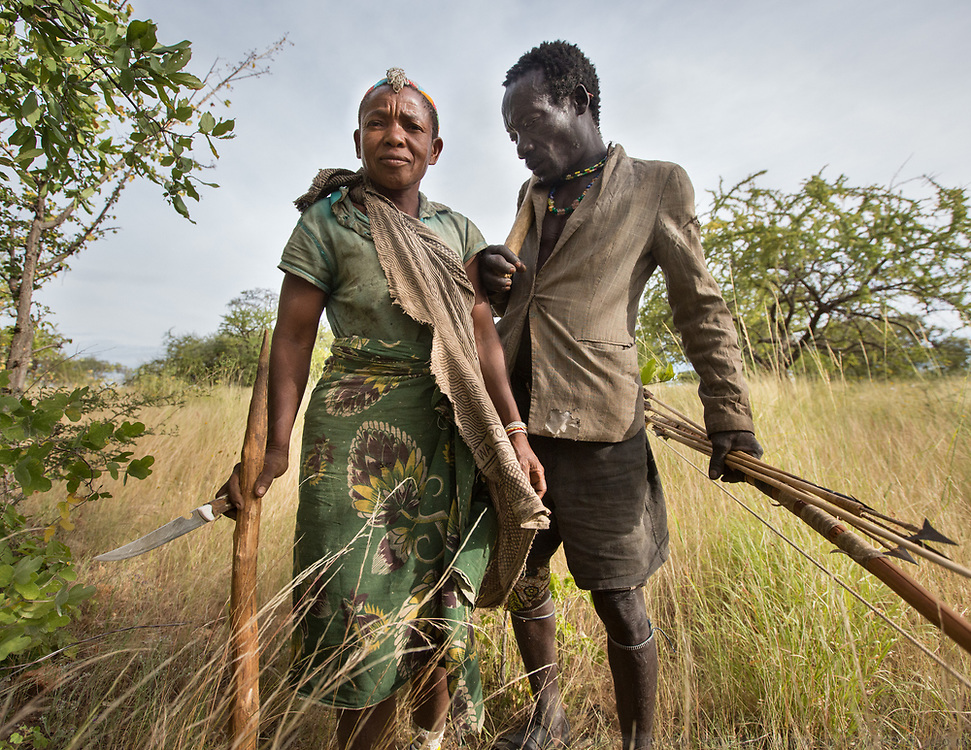 Wande and her husband, Mokoa, set out to find food. She uses a blade-tipped stick to dig tubers, a staple food especially in the rainy season. He brings an axe to extract honey-comb from tree trunks and a bow and arrows for hunting and defense. At the Hadza camp of Senkele.