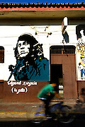 Bicycler rides past a revolutionary mural of a Sandinista painted on the side of a building in Leon, Nicaragua.