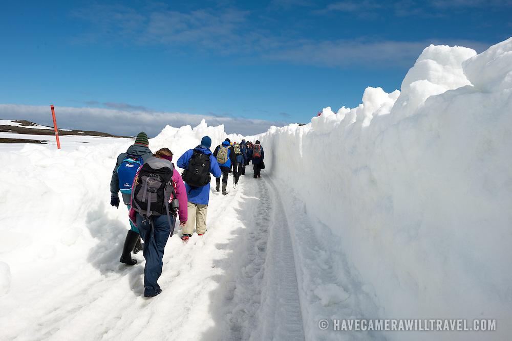 A line of tourists walking through along a makeshift roadway plowed through the deep snow towards the airstrip at Base Presidente Eduardo Frei Montalva on King George Island in Antarctica.