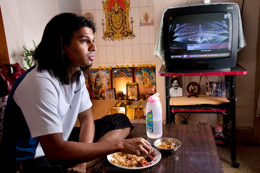 Shashi Kanth, a call center worker, eats a late lunch while watching MTV  at his home before going to work in Bangalore, India. (From the book What I Eat: Around the World in 80 Diets.) Shashi loves his mother's traditional southern Indian food at home, but when he's at work his dinner options are KFC and Beijing Bites, the fast-food restaurants on the ground floor of the high-rise where he works, located on the edge of Bangalore. Like many of his co-workers, Shashi relies on quick fast food meals, candy bars, and coffee, to sustain him through the long nights spent talking to westerners about various technical and billing problems. MODEL RELEASED.