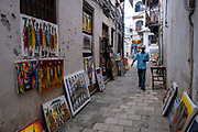 An artist promoting their art work to sell to tourists in Shangani, in the heart of Stone Town, Zanzibar, Tanzania.