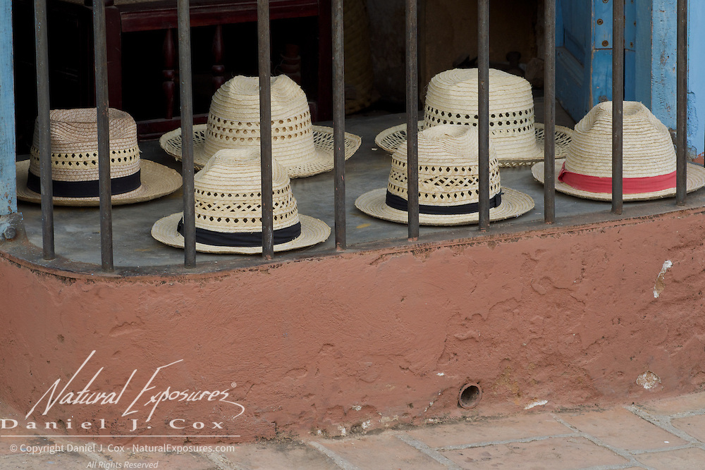 hats for sale in the window sill of a Trinidad, Cuba Store.