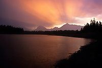 A fiery sunset rainstorm passes over Jackson Lake in Grand Teton National Park, Jackson Hole, Wyoming.