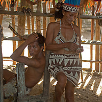 Amazon Indians of the Bora tribe near Iquitos, Peru prepare to dance for tourists - often a sideline to more modern workaday jobs.
