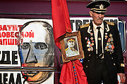 Moscow, Russia, 01/05/2005..Demonstrators from a wide range of political groups take to the streets on the traditional Russian Mayday holiday to protest against President Vladimir Putin and the Russian government..A naval veteran holdsa portrait of Stalin in front of a poster mocking President Putin.