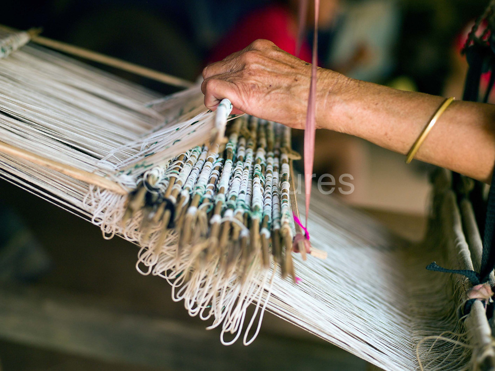 A Tai Lue woman weaving traditional bed sheets, Ban Ngay Neua village, Phongsaly province, Lao PDR. One of the most ethnically diverse countries in Southeast Asia, Laos has 49 officially recognised ethnic groups although there are many more self-identified and sub groups. These groups are distinguished by their own customs, beliefs and rituals.