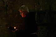 Praying with candlelight. Photographed in the Interior of the church of the Holy Sepulchre, Old city, Jerusalem, Israel