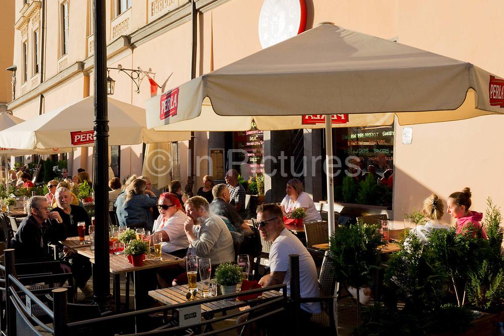 Visitors enjoy afternoon sunshine in a street cafe on Rynek Glowny market square, on 23rd September 2019, in Krakow, Malopolska, Poland.