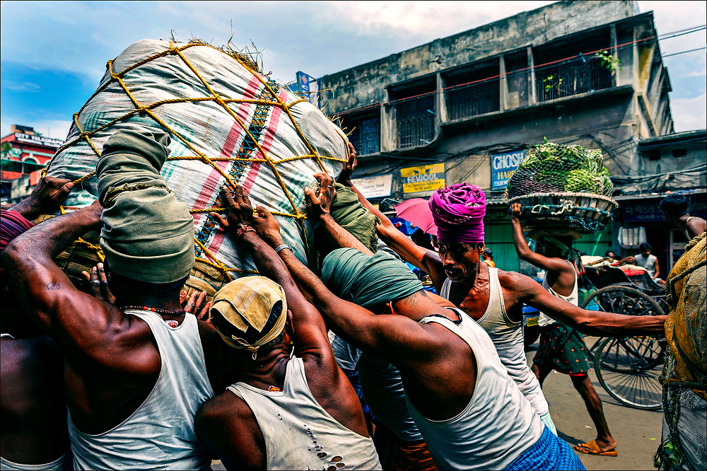 """Called """"human forklifts,"""" porters from India's Bihar state wrestle bundles weighing hundreds of pounds onto the turban-wrapped heads of fellow workers at the Kolay Market in the decrepit metropolis of Calcutta in West Bengal. Many Indians fear the entry of giant retailers such as Walmart and Tesco, with their state-of-the-art supply chains, would threaten traditional markets wholesale markets and retail shops.  © Steve Raymer / National Geographic Creative"""