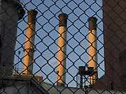 upward view of smoke stacks behind fence