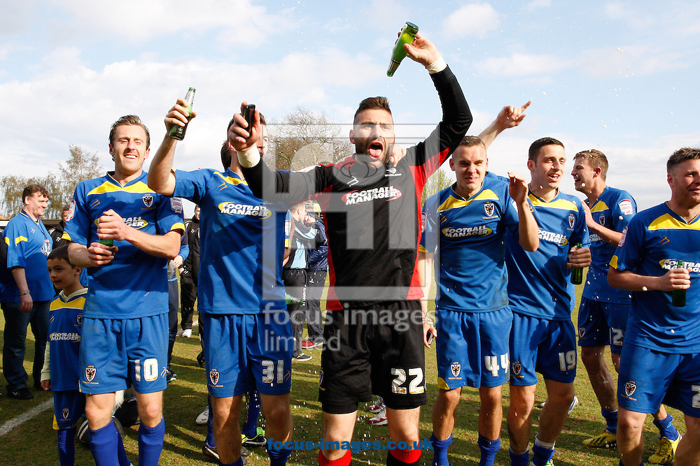 Picture by Andrew Tobin/Focus Images Ltd +44 7710 761829.27/04/2013. John Sullivan of AFC Wimbledon (C) and other players celebrate after winning 2-1 and staying up during the npower League 2 match at the Cherry Red Records Stadium, Kingston.