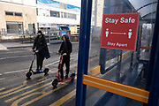 With local coronavirus lockdown measures in place and Birmingham currently set at 'Tier 2' or 'high', young men on e-scooters pass bus stops in the city centre, where social distancing measures and signs are in place on 26th October 2020 in Birmingham, United Kingdom. The three tier system in the UK has levels: 'medium', which includes the rule of six, 'high', which will cover most areas under current restrictions; and 'very high' for those areas with particularly high case numbers. Meanwhile there have been calls by politicians for a 'circuit breaker' complete lockdown to be announced to help the growing spread of the Covid-19 virus.