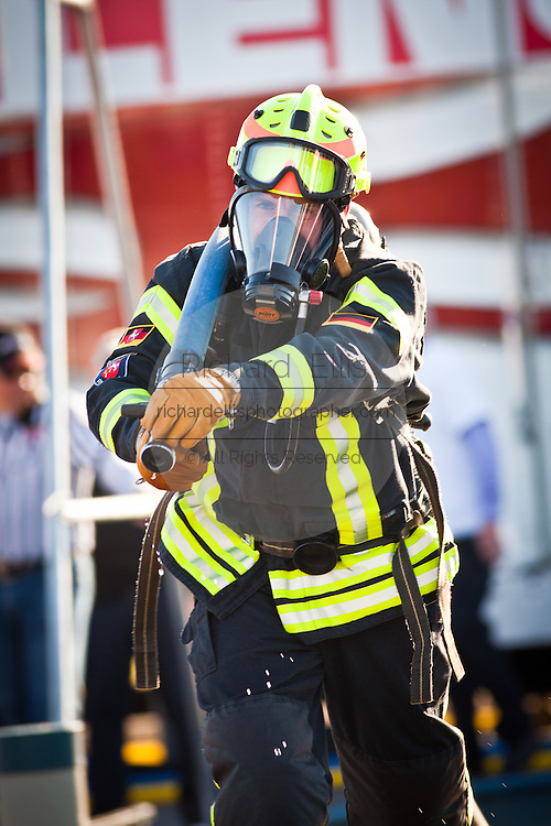 A firefighter races with a firehose while wearing full firefighting gear and working against the clock during the international finals of the Firefighter Combat Challenge on November 18, 2011 in Myrtle Beach, South Carolina.