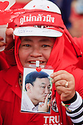 """26 MARCH 2009 -- BANGKOK, THAILAND: A supporter of deposed Thai Prime Minister Thaksin Shinawatra holds up a photo of Thaksin during a demonstration in favor of returning Thaksin to power. More than 30,000 members of the United Front of Democracy Against Dictatorship (UDD), also known as the """"Red Shirts""""  and their supporters gathered on Sanam Luang (the vast open field in front of the Palace) and descended on central Bangkok March 26 to start a series of protests against and demand the resignation of current Thai Prime Minister Abhisit Vejjajiva and his government. The protest is a continuation of protests the Red Shirts have been holding across Thailand. Thaksin was deposed in a coup and went into exile rather than go to prison after being convicted on corruption charges. He is still enormously popular in rural Thailand.  PHOTO BY JACK KURTZ"""