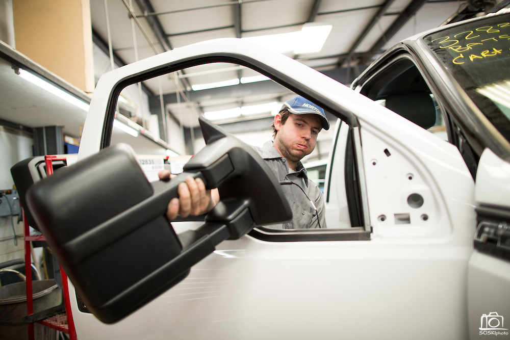 Body Tech Scott Ingraham installs a side mirror on a Ford pickup truck at T.G.I.F. Body Shop, Inc., in Fremont, California, on April 17, 2014. (Stan Olszewski/SOSKIphoto)