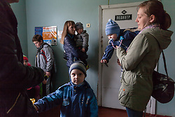 Svetlana Mulik, 38, with Alexander, 3 yr 7 month (l) Tatiyana Alekseeva, 34, and Sasha, 9 months (r) wait to see the MSF paediatrician at Bolshaya Vergunka polyclinic in Lugansk.