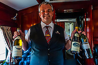 A waiter serving wine during lunch in the pillared pre-1940s dining car on the luxury Rovos Rail train between Pretoria and Cape Town, South Africa.