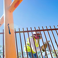 """101812       Cable Hoover<br /> <br /> City of Gallup Parks Department employee Leon Cunejo uses a sprayer to paint the fences at Fr Dunstan Park in Gallup Thursday. """"I just want to get everything finished up"""" said Cunejo, whose seasonal employment term is nearly finished."""