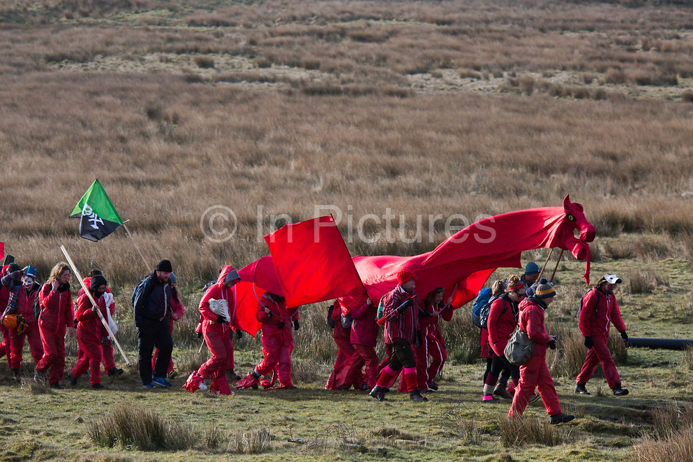 Hundreds of environmental activists stopping the open cast coal mine Ffos-y-Fran near Merthyr Tydfil, Wales from operating May 3rd 2016. Climate activists heading towards the mine with a a red Welsh dragon. The activists from Reclaim the Power wants the mine shut down and a moratorium on all future open coal mining in Wales. The group Reclaim the Power had set up camp near by and had over three days prepared the action and up to 300 activists all dressed in red went into the mine in the early morning. The activist were plit in three groups and carried various props signifying the red line in the sand, initially drawn in Paris at the COP21. The mine is one of the largest open cast coal mines in the UK and is run by Miller Argent who have to date extracted 5million tons of coal. The activists entered the mine unchallenged by any security or police and the protest went on peacefully till mid afternoon with no arrests made.  Open coal mining is hugely damaging to the local environment and  contributing to global climate change.