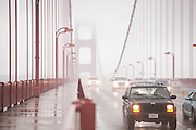 Cars drive through heavy rain and fog on Golden Gate Bridge in San Francisco, California.