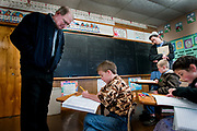 James Rhodes looks over his son, Glenn's schoolwork during a visit to the school. Children attend school from grades one through eight using curriculum written by members of the Mennonite faith. While basic education is important, the most necessary life-lessons are believed to be taught in the home and church. The school has two classrooms. One for grades 1-4 and the other for grades 5-8.
