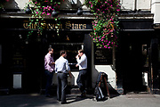 Smartly dressed men drinking beer outside The Seven Starts, a famous old pub in Lincoln's Inn Fields, London. This area is where many of the law courts are based in addition to offices of those involved in the law business.