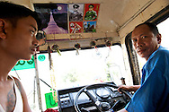 A driver and ticket inspector wait for passengers to fill the bus. Images of General Aung San sit next to the sacred Shwedagon Paya..Yangon, Myanmar. 2012