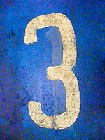 numeral three painted on a weathered surface