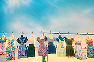 mannequins hung on a metal pole at a music festival wearing summer clothes for women