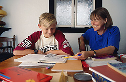 Woman teaching young boy at home,