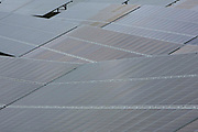 A close up view of photovoltaic solar panels at different angles in a field for electricity production.Salhouse Solar Park has an electrical output of 4.987 MW saving emissions of 4890 tonnes of C02 per year. Norfolk. UK.