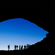 Photographers stand silhouetted in Arches National Park Utah.