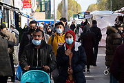 As Londoners from the mainly Bangladeshi Asian community await the second coronavirus national lockdown it's business as usual at Whitechapel Market with people out and about, some wearing face masks and some not, on what will be the last few days of normality before a month-long total lockdown in the UK on 2nd November 2020 in London, United Kingdom. The three tier system in the UK has not worked sufficiently, to suppress the virus, and there have have been calls by politicians for a 'circuit breaker' complete lockdown to be announced to help the growing spread of the Covid-19.