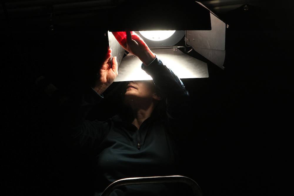Volunteer Laura Ayers, working as lighting director, adjusts a light for the filming of The Judy Corrao Show at The Minneapolis Television Network in Minneapolis December 12, 2012.