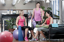 Three smiling women in a gym
