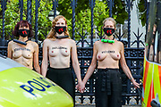 A police van is parked up in front of Topless Climate activists who locked themselves against the railings of the Houses of Parliament, during an Extinction Rebellion (XR) protest, in London on Thursday, Sept. 10, 2020. Environmental nonviolent activists group Extinction Rebellion enters its 10th and final day of continuous ten days protests to disrupt political institutions throughout peaceful actions swarming central London into a standoff, demanding that central government obeys and delivers Climate Emergency bill. (VXP Photo/ Vudi Xhymshiti)
