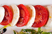 A caprese salad served at a hotel-restaurant in Montepulciano, Tuscany, Italy. Tomatoes, mozzarella, olive oil, balsamic vinegar, arugula. Food photography.