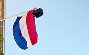 Nederland, Scheveningen, 22-6-2018 Nederlandse vlag schooltas is uitgehangen om te vieren dat het eindexamen is gehaald. Deze week hebben scholieren van het voortgezet onderwijs de uitslag van hun eindexamen gekregen. Bij veel geslaagden gaat traditioneel de vlag uit, met de boekentas aan het einde van de stok. Foto: Flip Franssen