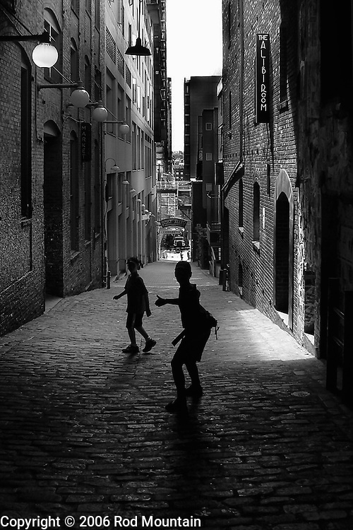 Two young boys stop and turn to look back as they make their way down Post Alley in Seattle, Washington. <br /> <br /> This photo has been recognized as a Nominee in the 10th Annual Black and White Spider Awards in the professional category of Silhouette. <br /> <br /> http://www.thespiderawards.com/10thshow/nominations.php?x=p&cid=295<br /> <br /> Photo: © Rod Mountain<br /> <br /> www.rodmountain.com