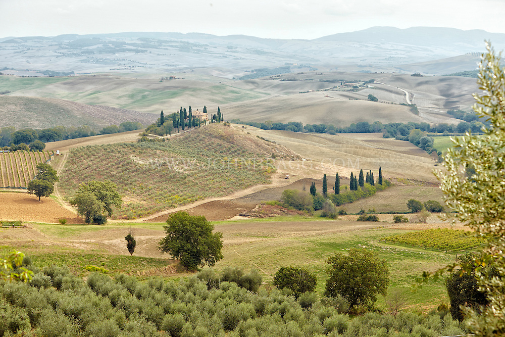 Photo of a beautiful Italian villa surrounded by colorful Tuscan farmland in Val d'Orcia, Italy.
