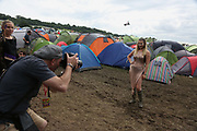Heavy rain creates the familiar muddy base as a male photographer photographs a woman in wellies at Glastonbury Festival in Glastonbury, United Kingdom. Glastonbury Festival is a five-day festival of contemporary performing arts that takes place near Pilton, Somerset. In addition to contemporary music, the festival hosts many other arts. (photo by Kristian Buus/In PIctures via Getty Images)